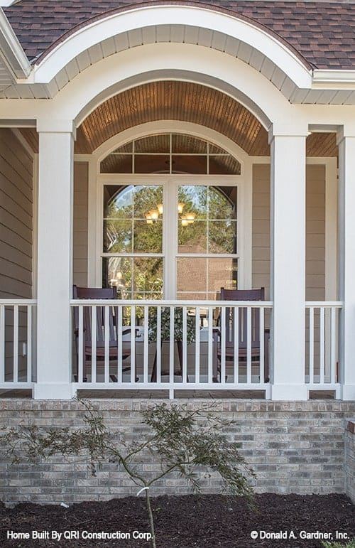 Home's front porch defined with a decorative archway. It is filled with wooden chairs and a matching side table.