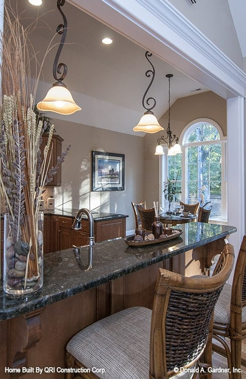 The black granite top peninsula is complemented with wicker counter chairs and ornate pendant lights.