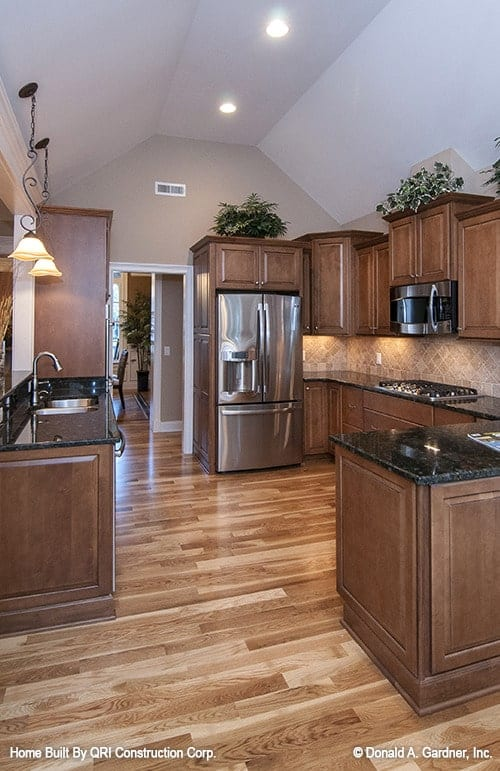 The kitchen has polished hardwood flooring and a white vaulted ceiling fitted with recessed lights.