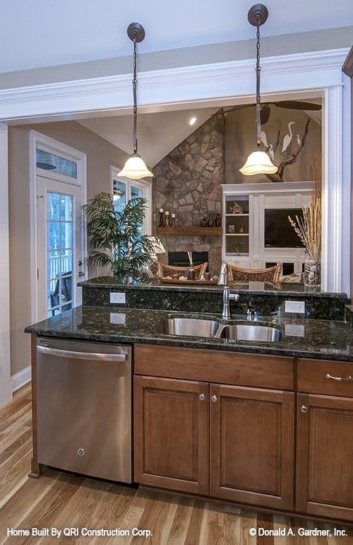 The two-tier peninsula facing the living area is fitted with a dual sink, stainless steel oven, and wooden cabinets.