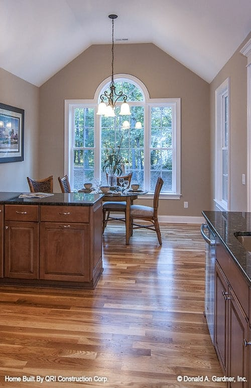 Breakfast nook across the kitchen with a warm chandelier and a round glass top table surrounded by cushioned chairs.