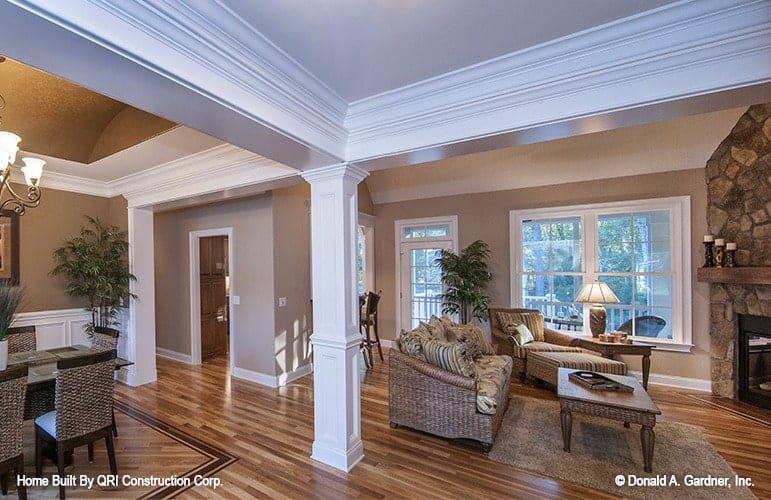 The open layout view shows the living room and formal dining room defined by a decorative column.