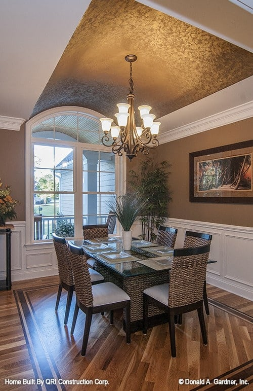 The formal dining room has a barrel-vaulted ceiling and brown walls adorned by a framed artwork and white wainscoting.