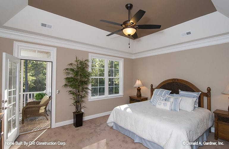 Primary bedroom with a brown tray ceiling and a glazed door that opens out to the screened porch.