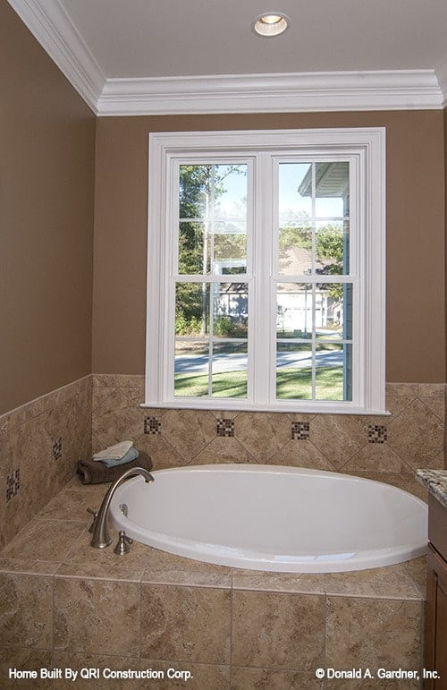 A drop-in tub clad in brown marble tiles and fixed under the white framed window.