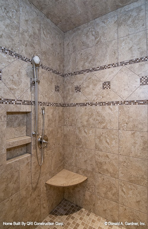 Shower area with mosaic flooring and brown tiled walls fitted with inset shelves and a corner tiled seat.
