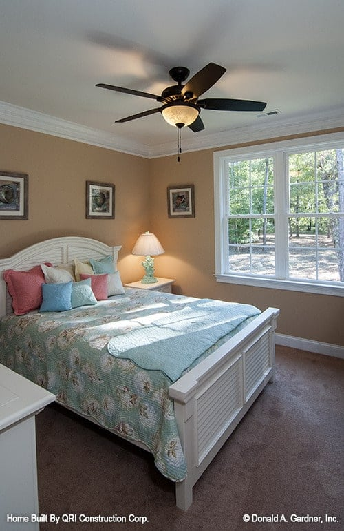 This bedroom features white furnishings that create a stunning contrast to the brown walls and carpet flooring.