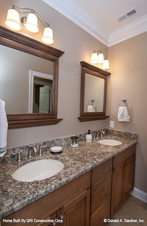 This dual sink vanity has a granite countertop and wooden framed mirrors lit by warm glass sconces.
