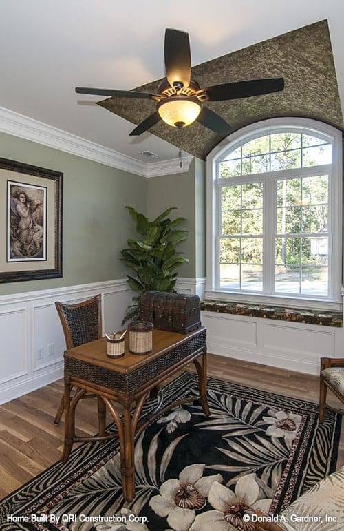 Home office with green and white wainscoted walls, arched window, and hardwood flooring topped with a black floral rug.