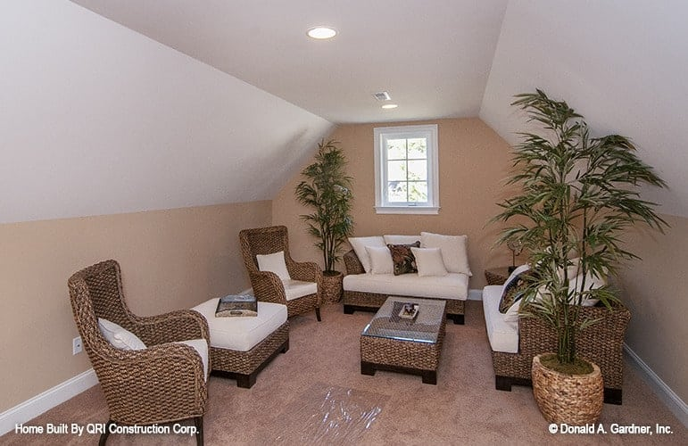 Tall potted plants, a glass top table, and wicker seats topped with white cushions and pillows fill the bonus room.