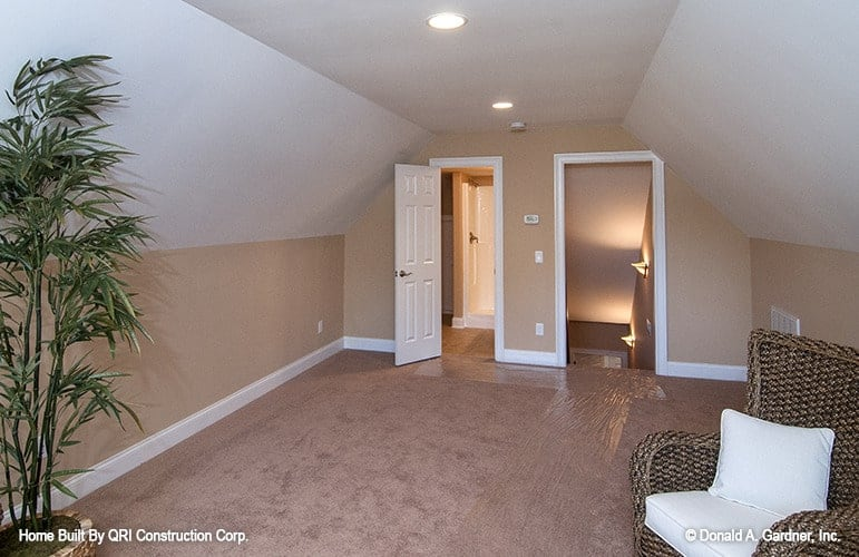 The bonus room has a vaulted ceiling and brown walls matching with the carpet flooring.