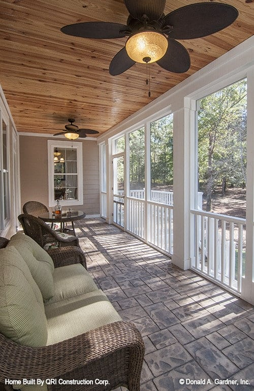 The screened porch is framed with white railings and decorative columns.
