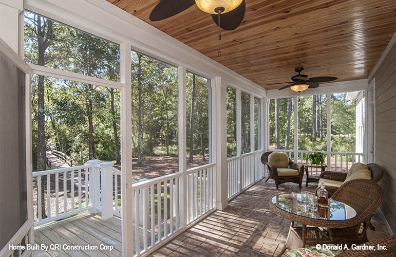 The screened door of the covered porch opens out to a staircase leading to the outdoors.