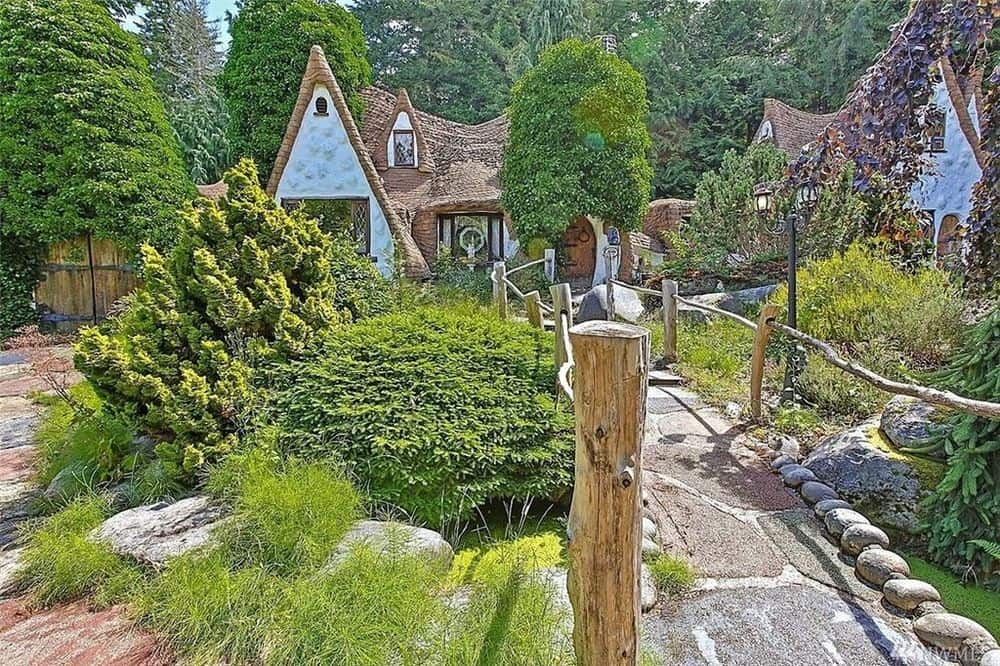 The stone bridge, walkways and lush landscaping surrounding the cottage completes the aesthetic of the fairy tale look. Images courtesy of Toptenrealestatedeals.com.