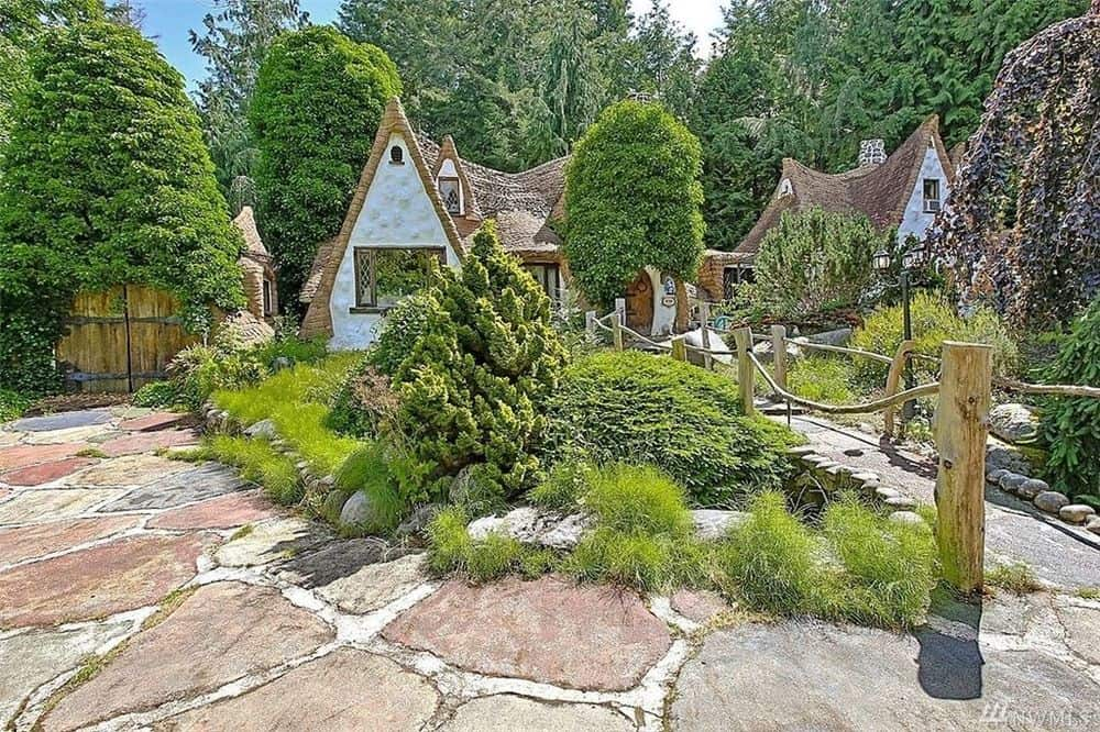 This angle shows you how the fantastical cottage is complemented by the surrounding lush mature trees, shrubs and grass. Images courtesy of Toptenrealestatedeals.com.