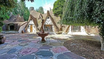 This is the front view of the cottage that has a colorful stone courtyard that creates a fantastical foreground for the eclectic cottage. Images courtesy of Toptenrealestatedeals.com.