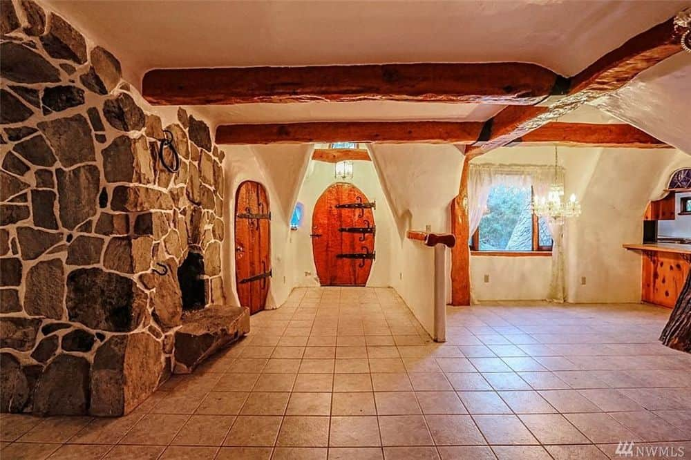 From the vantage of the large stone oven, you can see the couple of charming wooden doors that match the exposed wooden beams supported by the wrought iron hinges. Images courtesy of Toptenrealestatedeals.com.
