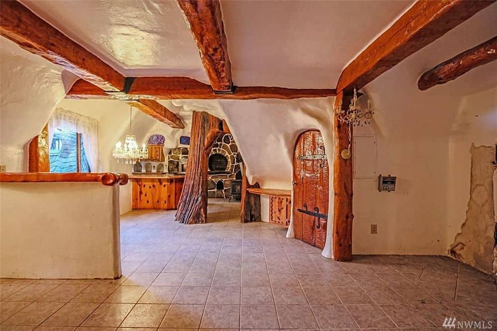 The kitchen can be clearly seen from the vantage of the foyer that has unique uneven beige ceiling with exposed wooden beams matching the columns. Images courtesy of Toptenrealestatedeals.com.