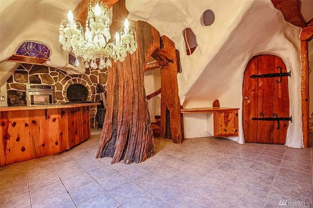 This angle of the kitchen shows the large tree trunk-like hand-carved pillar next to the majestic and warm chandelier in the middle of the large open room. Images courtesy of Toptenrealestatedeals.com.