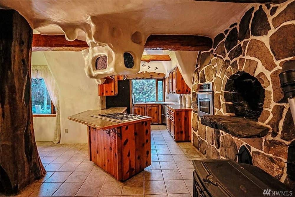 The kitchen also has a wooden kitchen island next to the large stone oven that stands out against the beige ceiling and floor tiles. Images courtesy of Toptenrealestatedeals.com.