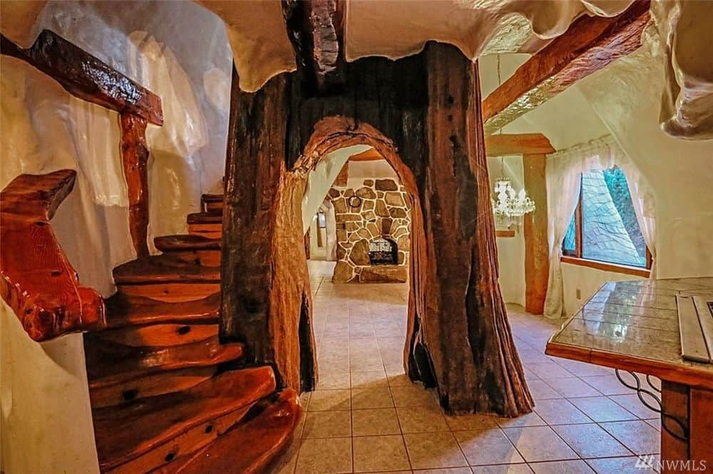 This is a closer look at the wooden staircase complemented by a large archway that has thick hand-carved columns. Images courtesy of Toptenrealestatedeals.com.