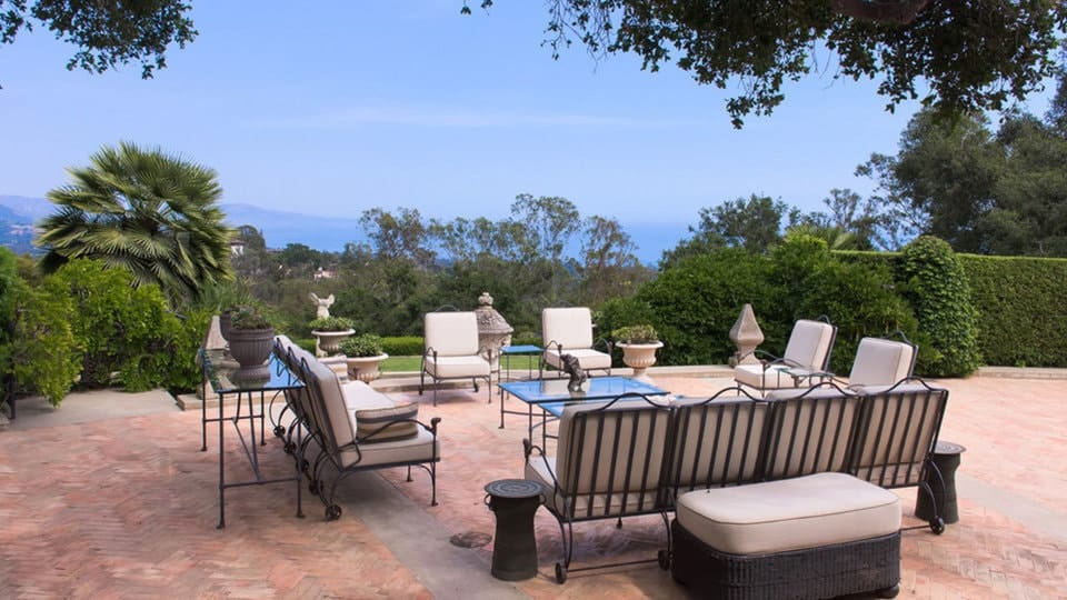 The outdoor patio of the mansion has lovely terracotta walkways with herringbone patterns to complement the simple outdoor sofa set that has beige cushions surrounding a couple of glass-top wrought iron coffee tables. Images courtesy of Toptenrealestatedeals.com.