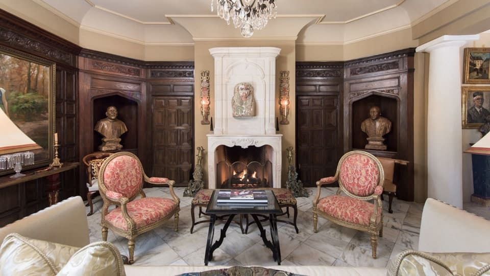 This living room has a comfortable sofa facing the two classic cushioned arm chairs by the fireplace that has a beige mantle topped with eclectic wall artworks that matches with the couple of busts in alcoves embedded into the dark wooden walls flanking the fireplace. These are all topped with a majestic crystal chandelier. Images courtesy of Toptenrealestatedeals.com.