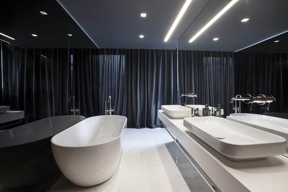 This is a simple bathroom with a black wall and black curtains on the far side. These are then contrasted by the white freestanding bathtub, white modern floating vanity and white flooring.