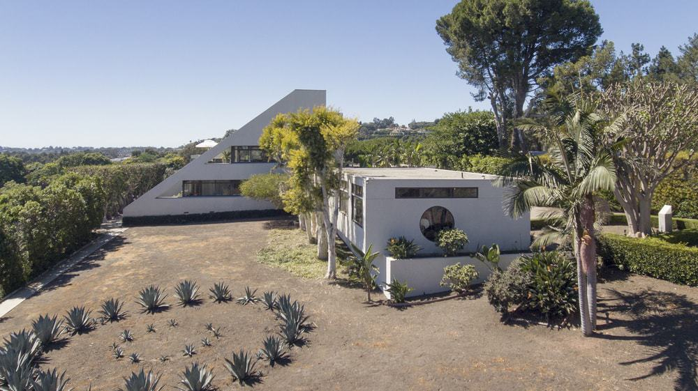 This aerial view of the property shows the two structures of the compound with white exterior walls complemented by the windows and the surrounding lush vegetation of the landscaping. The best part is the eclectic wedge-shaped building in the distance. Images courtesy of Toptenrealestatedeals.com.