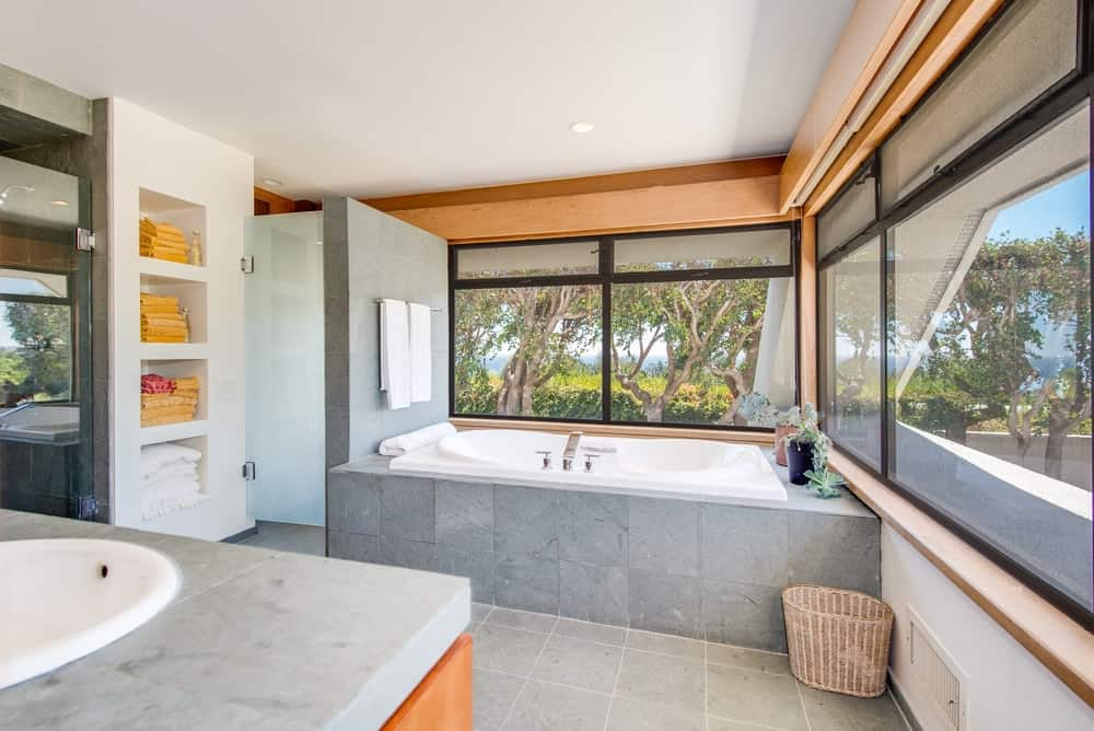 The bathroom also has a large bathtub placed at the corner surrounded by natural lights coming in from the rows of windows with black frames to stand out against the wooden tone of the upper wall. Images courtesy of Toptenrealestatedeals.com.