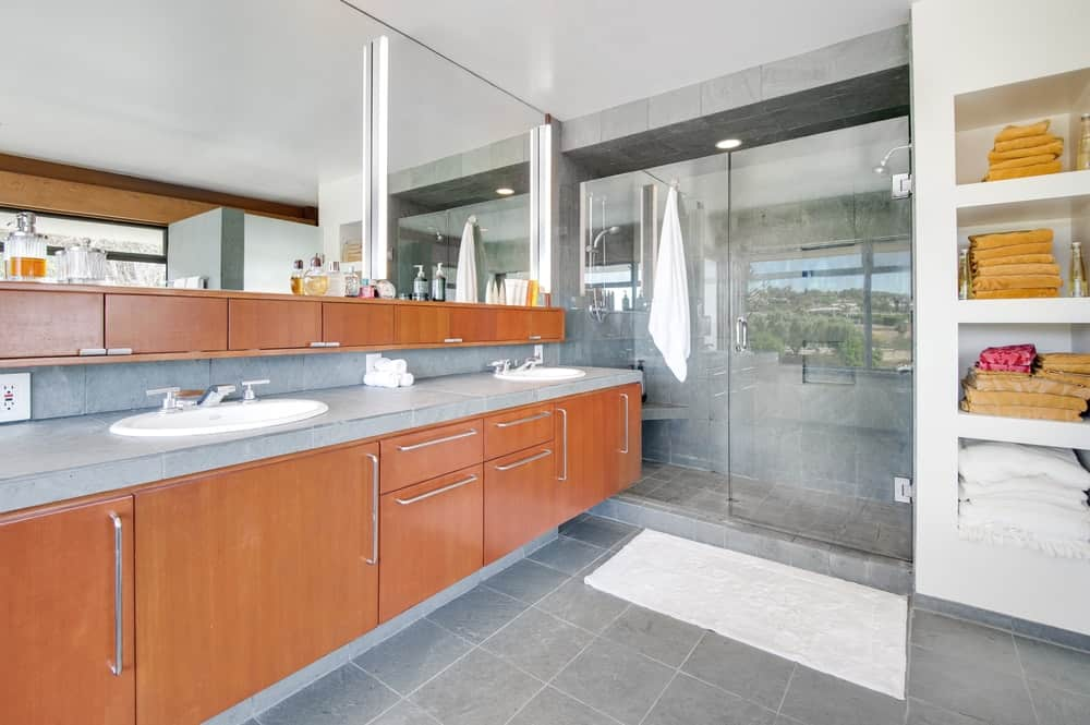 The primary bathroom has a modern and sleek floating two-sink vanity paired with a wide wall-mounted mirror next to the glass-enclosed shower area. Images courtesy of Toptenrealestatedeals.com.