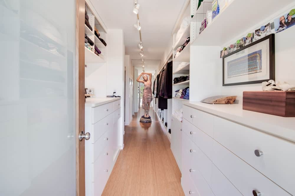 A narrow light hardwood flooring gives a homey feel to the white wooden structures on the walls of the walk-in closet that has shelves, cabinets and drawers. Images courtesy of Toptenrealestatedeals.com.