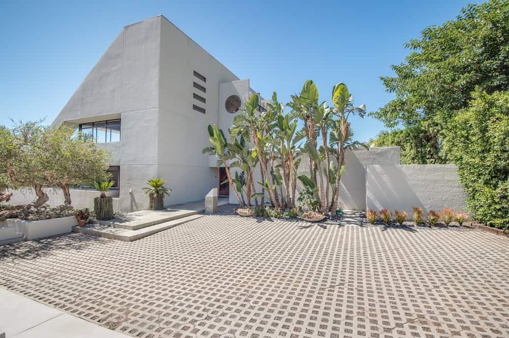 This is the front of the house with a spacious parking area adorned with various tropical trees and shrubs to contrast the white textured exteriors of the wedge-shaped home. Images courtesy of Toptenrealestatedeals.com.