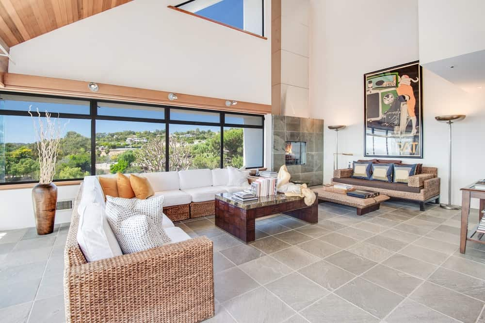 The living room is dominated by a large L-shaped woven wicker sofa paired with a wooden coffee table and a fireplace embedded into the wall. Images courtesy of Toptenrealestatedeals.com.