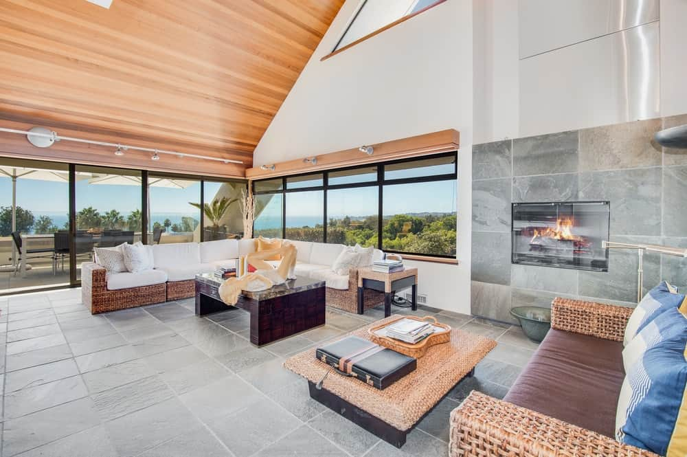 This is the spacious and airy living room bathed in natural light from the glass windows under the tall wooden cathedral ceiling. Images courtesy of Toptenrealestatedeals.com.