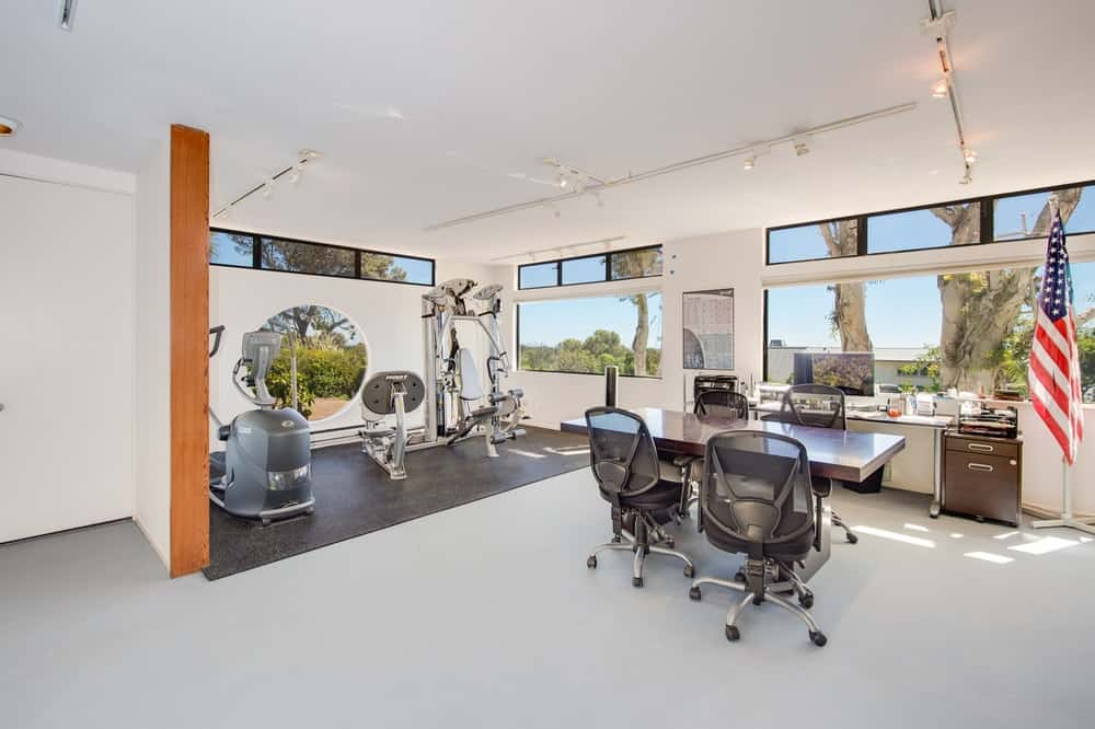 This is the simple and charming home office and gym. The office has a large dark wooden desk and main table paired with modern swivel chairs. The small gym on the side has a few machines facing a circular window. Images courtesy of Toptenrealestatedeals.com.