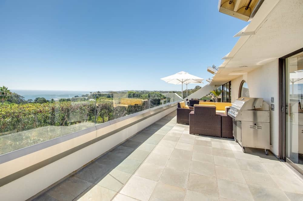 A seen from the circular window, the patio is locate on a large terrace with woven wicker arm chairs and a grilling station beside it. Images courtesy of Toptenrealestatedeals.com.