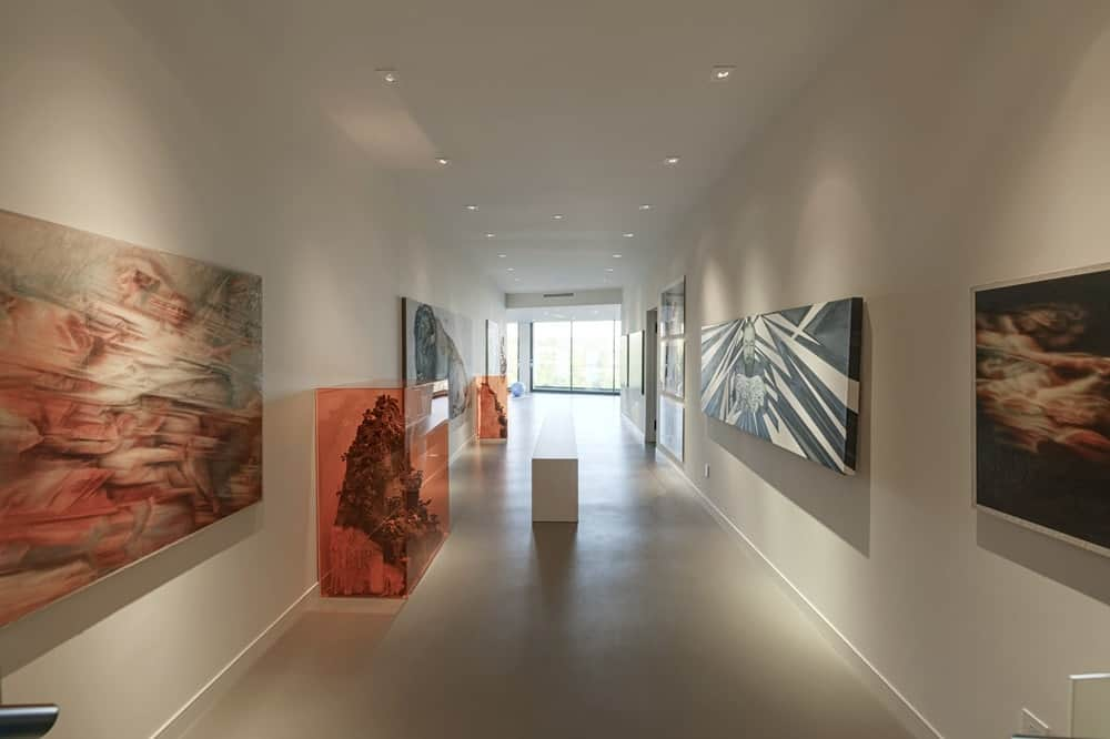 This home also has a large space that is perfect for an art gallery to display your art collection. It has beige walls and matching tall beige ceiling with recessed lights and spot lights to illuminate the displayed artworks. Images courtesy of Toptenrealestatedeals.com.