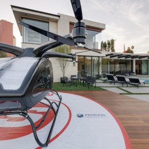 This view of the Starview Estate from the backyard shows the modern Contemporary-style home with wrap-around glass windows at the second level and an abundance of retractable glass walls on the main level that opens up to the backyard that has a pool and a helipad with a two-passenger drone helicopter.