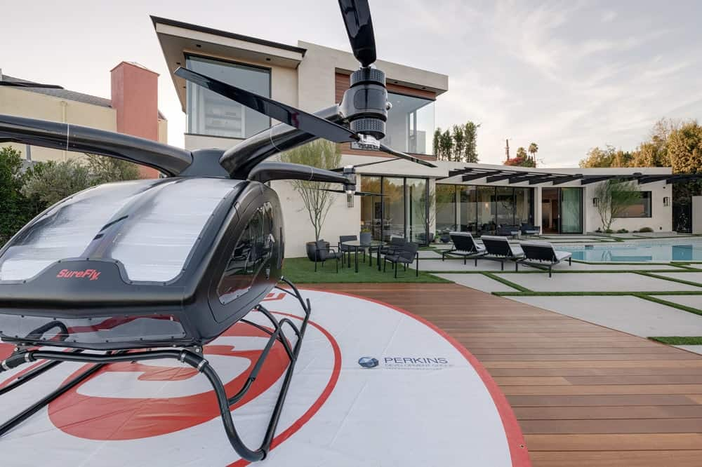 This view of the Starview Estate from the backyard shows the modern Contemporary-style home with wrap-around glass windows at the second level and an abundance of retractable glass walls on the main level that opens up to the backyard that has a pool and a helipad with a two-passenger drone helicopter. Images courtesy of Toptenrealestatedeals.com.