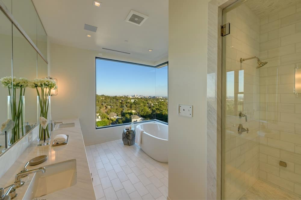 This bathroom of the house has a plain beige ceiling, walls and flooring tiles that are arranged in a charming and homey pattern. The two-sink vanity is topped with a large wall-mounted mirror complemented by wall-mounted lamps. Images courtesy of Toptenrealestatedeals.com.