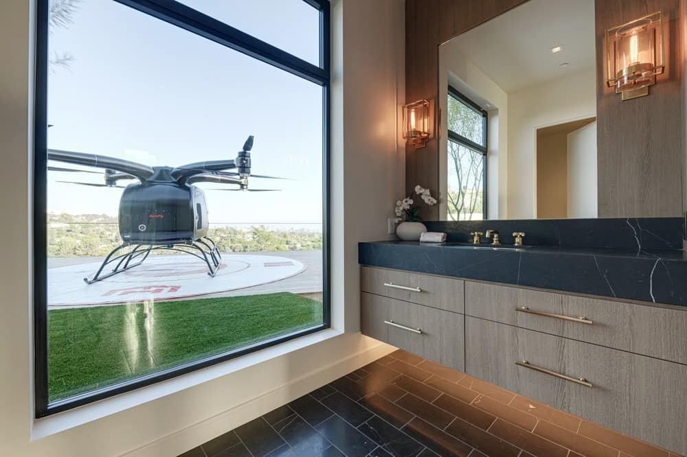 This ground level bathroom and powder room has a floating vanity with lights underneath that pair with those flanking the mirror. The highlight of this bathroom is the clear view of the helicopter parked on the helipad outside the glass window. Images courtesy of Toptenrealestatedeals.com.