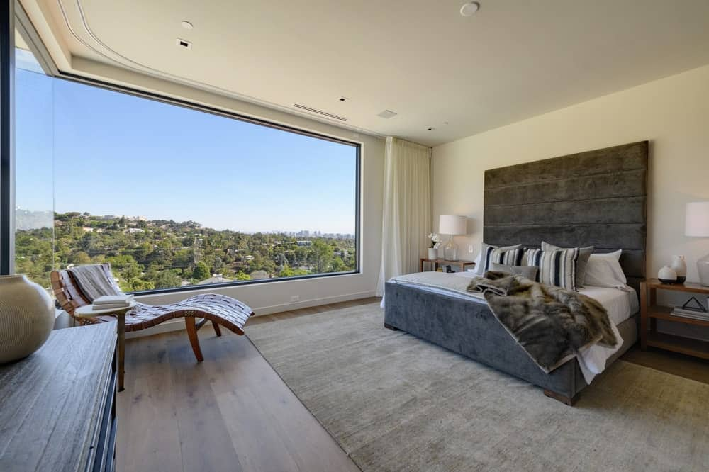 The large dark gray bed stands out in this bedroom with its large dark gray cushioned headboard flanked by bedside tables. The highlight of this bedroom is the wide and bright corner dominated by the glass walls that offer a scenic view. Images courtesy of Toptenrealestatedeals.com.