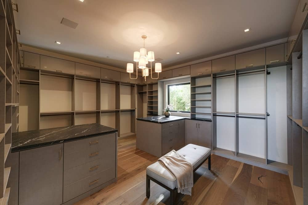 This beautiful walk-in closet has gray wooden structures on its walls that has shelves and cabinets. Images courtesy of Toptenrealestatedeals.com.