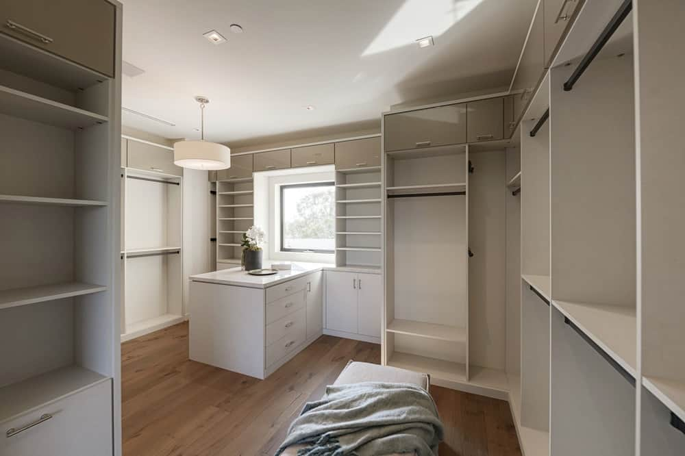 This other walk-in closet only has a simple semi-flush lighting that hangs over a countertop with drawers by the small glass window. The light tones of the wooden structures stand out against the dark hardwood flooring. Images courtesy of Toptenrealestatedeals.com.