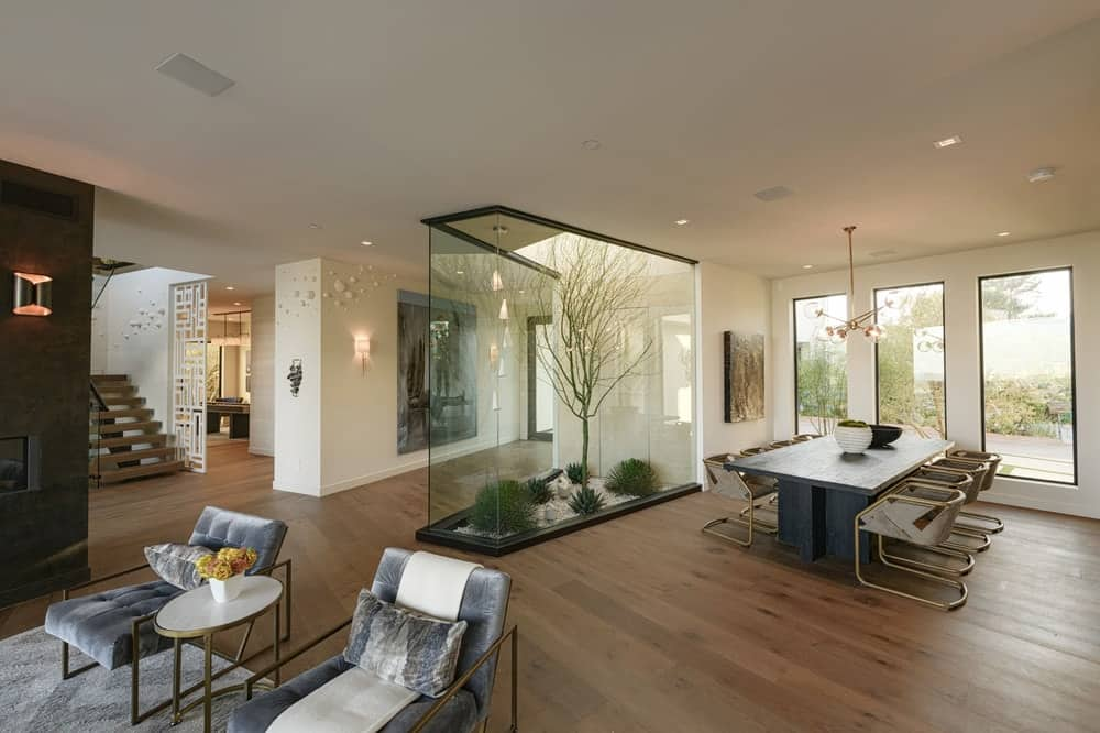This gorgeous dining room has dark hardwood flooring that contrasts the bright beige ceiling and walls. These also contrast the dark wooden dining table surrounded by modern dining chairs that have golden legs. The dining is also complemented with a glass-enclosed terrarium beside it. Images courtesy of Toptenrealestatedeals.com.
