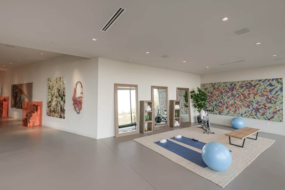 This marvelous home also has a spacious and bright personal gym with a light tone to its flooring to match the beige walls and ceiling. The area is adorned with a large wall-mounted abstract painting. Images courtesy of Toptenrealestatedeals.com.