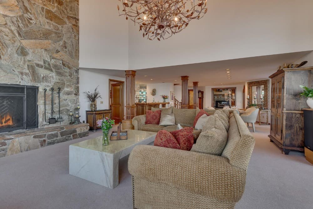 Another look at this living space showcasing its large and luxurious L-shaped sofa set along with a marble center table and a large stone fireplace. Images courtesy of Toptenrealestatedeals.com.
