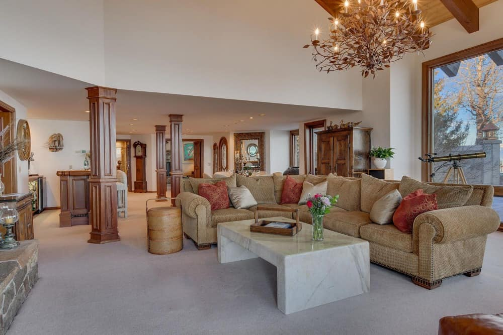 Another look at this living space with a massive stone fireplace and a large L-shaped sofa set with a marble center table. Images courtesy of Toptenrealestatedeals.com.