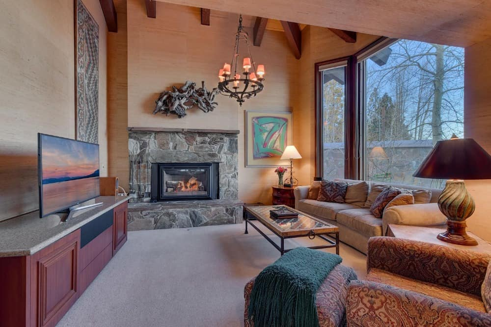 Family living space with a cozy couch, a large fireplace and a flat-screen TV set in front. Images courtesy of Toptenrealestatedeals.com.